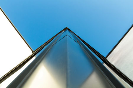 Corner detail of a modern building facade on a bright sunny day with clear sky. Abstract background. Space for text
