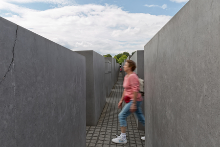 panning shot: BERLIN, GERMANY - JULY 2015: Woman walking in the Memorial to the Murdered Jews of Europe, also known as the Holocaust Memorial (German: Holocaust-Mahnmal) in Berlin, Germany