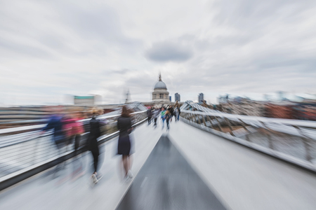 panning shot: Panning photograph of people walking on a the Millennium Bridge in London, with camera made motion blur