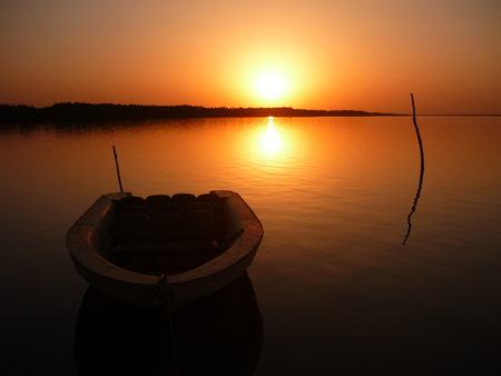 Boat on the Gambia river at sunset Stock Photo