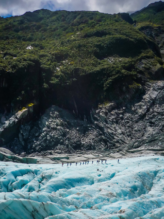 A group of tourists take a guided walk on Fox Glacier South Island New Zealand, amazing blue color of ice