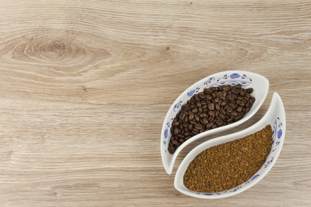 soluble: instant soluble coffee and coffee beans in a porcelain bowl on wooden background