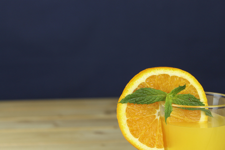 Homemade orange juice garnished with a mint leaf and a view of sliced orange in the glass. photo