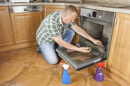 exertion: Man kneels on the floor in the kitchen and cleans the oven. Cleaning work in the home. Man helping his wife with maid service.