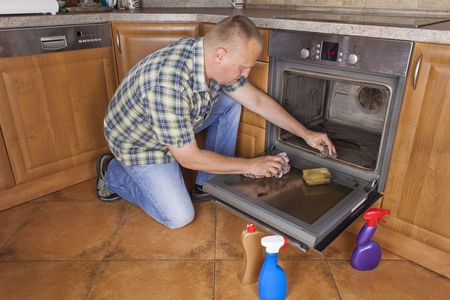 Man kneels on the floor in the kitchen and cleans the oven. Cleaning work in the home. Man helping his wife with maid service.