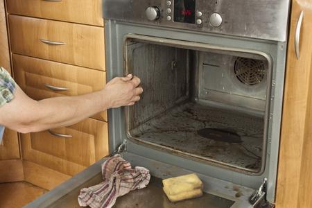 男は台所の床に跪いて、オーブンをクリーンアップします。家庭での清掃作業。男はメイド サービスと彼の妻を助けます。