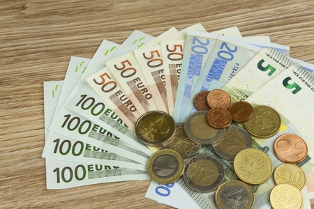 legal tender: Euro coins and banknotes on the table. Detailed view of the legal tender of the European Union EU. The uncertain future of the euro.