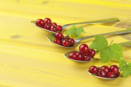 coffee spoon: Coffee spoon with red currants on a yellow wooden table. Preparing for home baking currant dessert. Stock Photo
