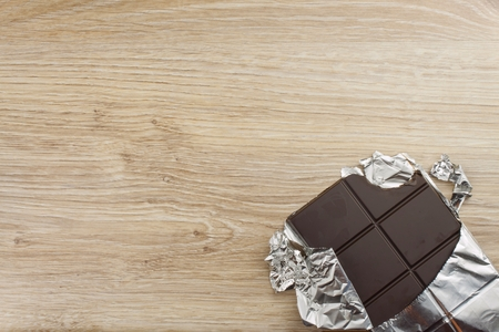 sweet treat: Chocolate wrapped in aluminum foil on a wooden board. Wrapped sweet treat.