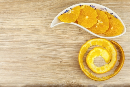 orange peel skin: peeled and sliced orange in a porcelain bowl on the table. Stock Photo