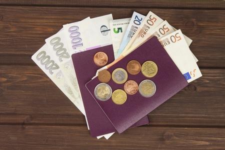 pasaporte: Pasaporte y dinero en la mesa de madera. Billetes válidos euro, monedas y billetes de banco checos. La migración ilegal de dinero. Pagar los contrabandistas para cruzar la frontera. Foto de archivo