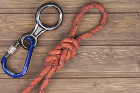 rappel: Figure eight knot with climbing carabiner and rappel eight on wooden background. The concept of selling advertising space for climbing equipment. Stock Photo