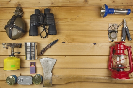 Preparing for summer camping. Things needed for an epic adventure. Sales of camping equipment. Packaging equipment for camping. Camping equipment on a wooden board. Standard-Bild