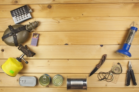 packaging equipment: Preparing for summer camping. Things needed for an epic adventure. Sales of camping equipment. Packaging equipment for camping. Camping equipment on a wooden board. Stock Photo