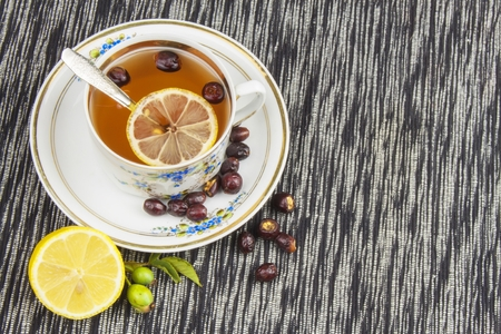 colds: Hot tea with lemon and red arrow in the table. Home treatment for colds and flu. Treating colds using traditional recipes. Stock Photo
