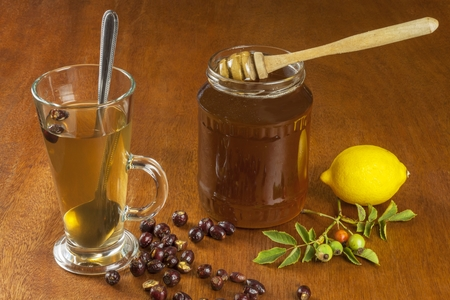 テーブルにレモンと赤矢印がある熱いお茶。風邪やインフルエンザのための在宅治療。伝統的なレシピを使用して風邪の治療。