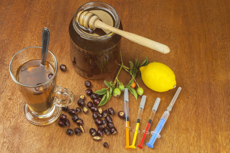 flu vaccination: Rosehip tea and flu vaccination. Traditional medicine and modern treatment methods. Injection of influenza vaccine. Household treatment of flu and colds.