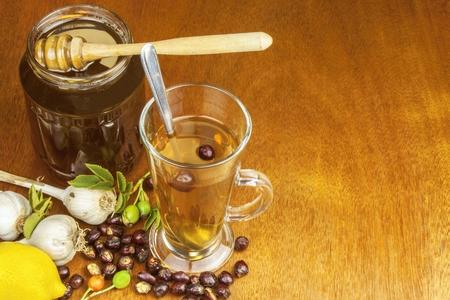 gripe: Tratamiento en el hogar tradicional para los resfriados y la gripe. T� de escaramujo, ajo, miel y c�tricos. T� caliente con miel y lim�n sobre una mesa de madera. Inicio Farmacia.