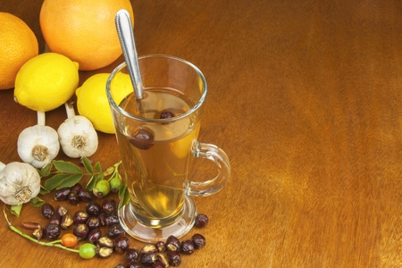 colds: Traditional home treatment for colds and flu. Rosehip tea, garlic, honey and citrus. Hot tea with honey and lemon on a wooden tabletop. Home Pharmacy. Stock Photo