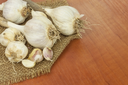 garlic cloves: Homemade garlic grown in the garden. Traditional medicine against colds and flu. Strongly aromatic vegetables for cooking. Healthy ingredients for cooks. Garlic cloves on a wooden kitchen table. Stock Photo