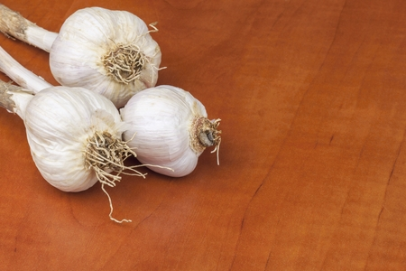 colds: Homemade garlic grown in the garden. Traditional medicine against colds and flu. Strongly aromatic vegetables for cooking. Healthy ingredients for cooks. Garlic cloves on a wooden kitchen table. Stock Photo