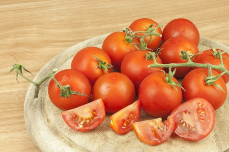ready to cook food: Fresh tomatoes on the kitchen table. Tomatoes on a wooden cutting board. Domestic cultivation of vegetables. Fresh organic food ready to cook. Fresh dietary ingredients. Raw vegetables to raw food.