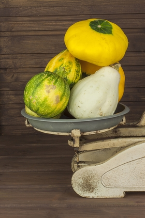 festival scales: Old kitchen scale vegetable. Autumn harvest of pumpkins. Preparing for Halloween. Growing vegetables in a home garden. Place for your text. Autumn pumpkins with leaves on wooden board