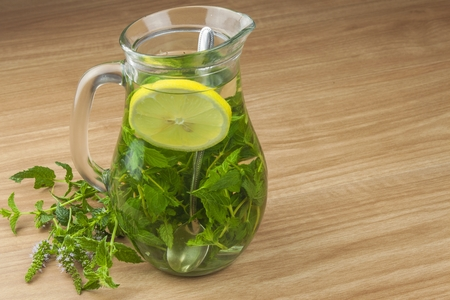 Fresh homemade mint tea. Tempting summer refreshment. Healthy, refreshing drink without sugar. Peppermint tea in a glass jar with lemon. Preparing tea. Imagens
