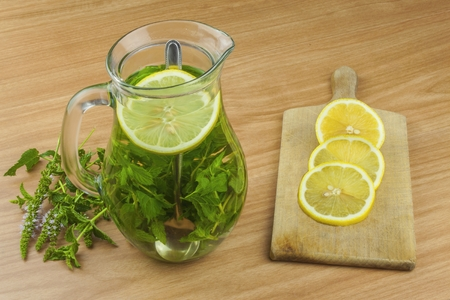 healthcare visitor: Fresh homemade mint tea. Tempting summer refreshment. Healthy, refreshing drink without sugar. Peppermint tea in a glass jar with lemon. Preparing tea. Stock Photo