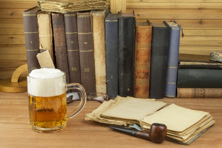 personas leyendo: Cool glass of beer on the table. Relax with a good book with a glass of cold beer. The concept relax with a good beer. Pouring a glass of beer for readers of the book. Alcohol and study.