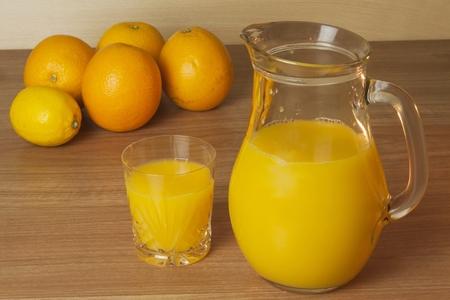 verre de jus d orange: Domestic jus d'orange frais dans un bocal de verre sur une table en bois. Main-maison pr�par�s jus d'orange. Boisson saine pour les athl�tes. Placez pour votre texte. Les ventes de jus de fruits.