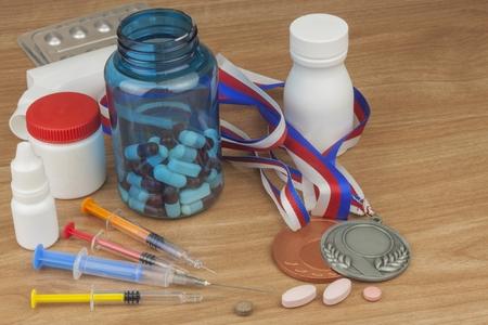 スポーツのドーピング。蛋白同化ステロイドのスポーツの悪用。蛋白同化ステロイドは、木製のテーブルにこぼした。スポーツの詐欺。製薬業界。 写真素材