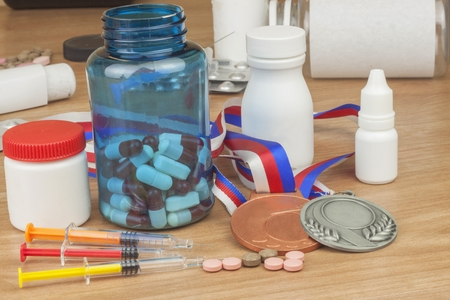 healthier: Doping in sport. Abuse of anabolic steroids for sports. Anabolic steroids spilled on a wooden table. Fraud in sports. Pharmaceutical industry. Detailed view of the medication. Place for your text. Stock Photo