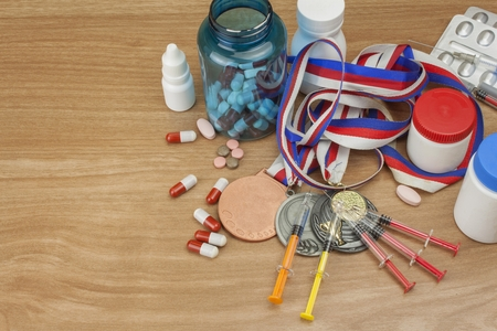 Doping in sport. Abuse of anabolic steroids for sports. Anabolic steroids spilled on a wooden table. Fraud in sports. Pharmaceutical industry. Sports fraud, fake winner. 版權商用圖片