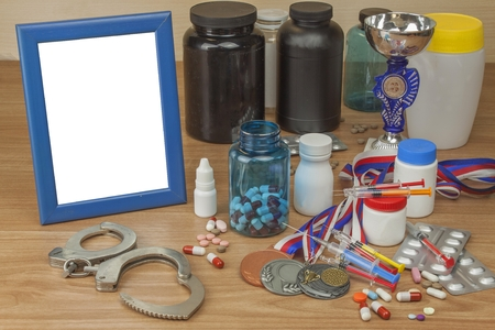 healthier: Doping in sport. Abuse of anabolic steroids for sports. Anabolic steroids spilled on a wooden table. Fraud in sports. Pharmaceutical industry. Sports fraud, fake winner. Stock Photo