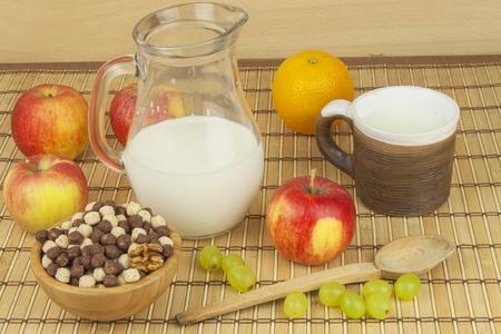 nutricion: Bolas de cereales de chocolate en un plato de bamb�. Desayuno saludable con frutas y leche. Una dieta llena de energ�a y fibra para los atletas. R�pida para preparar el desayuno casero.
