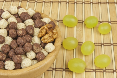 chocolate cereal: Chocolate cereal balls in a bowl of bamboo. Healthy breakfast with fruit and milk. A diet full of energy and fiber for athletes. Quick to prepare homemade breakfast. Stock Photo