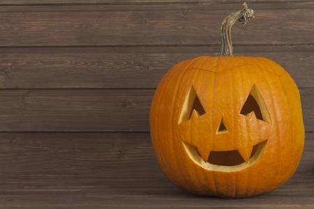 pumpkin head: Halloween pumpkin head on wooden background. Preparing for Halloween. Head carved from a pumpkin on Halloween. Pumpkin tradition. Place for your text. Invitation for halloween. Scary Halloween pumpkin