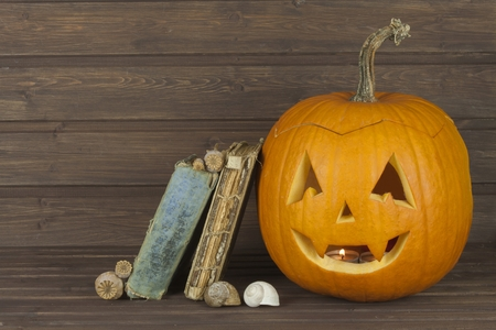 spells: Halloween pumpkin head on wooden background. Preparing for Halloween. Head carved from a pumpkin on Halloween. Pumpkin tradition. The book of spells, magical book.  Textbooks for witches. Stock Photo