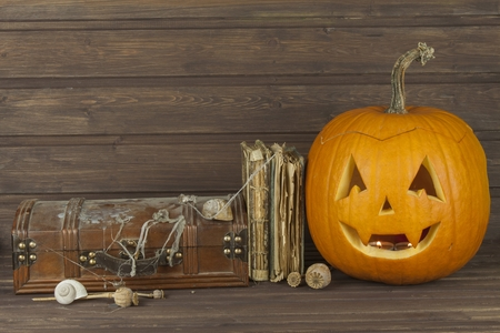wood spider: Finding a mysterious wooden box. Mystery enclosed in the cabinet. Retro look of ancient box like pirate treasure chest. Invitation for halloween. Scary Halloween pumpkin. The book of arcane magic Stock Photo