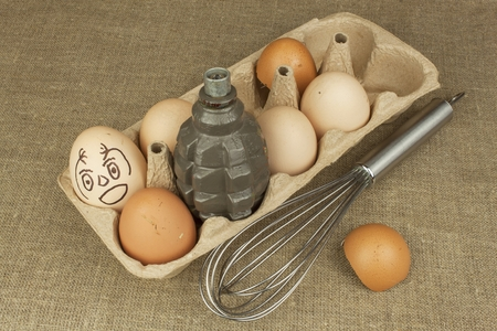 duck egg: Hand grenade - an egg. Grenade between eggs. Explosive eggs, funny picture. Homemade chicken eggs. Traditional food with protein. Eggs on the table, food preparation. Preparing egg omelet.
