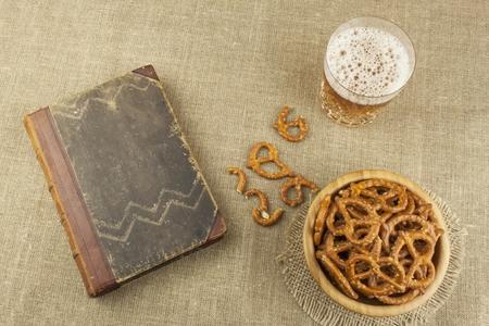 ver television: La cerveza en un vaso y un libro sobre la mesa. paja de trigo crujiente con sal. La pila de palitos de pretzel. Entretenimiento para ver la televisi�n. Foto de archivo