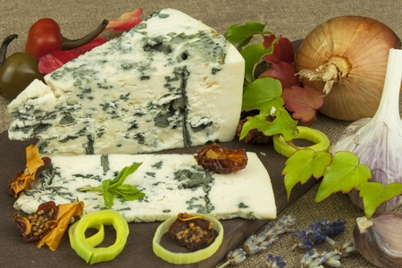 stilton: Cheese with mold on a wooden cutting board. Preparation of aromatic cheese. Stilton cheese on wooden cheese board. Slices of Danish Blue cheese on an table. Stock Photo