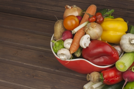 Vegetables in a red bowl on the table, instead of text. Various types of vegetables on an old wooden table. The concept of diet food. Food for obese patients. Autumn harvest vegetables.