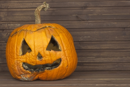 pumpkin head: End of Halloween, Moldy pumpkin. Remembering Halloween. Head carved from a pumpkin on Halloween. Pumpkin tradition. Place for your text. Invitation for halloween. Scary Halloween pumpkin