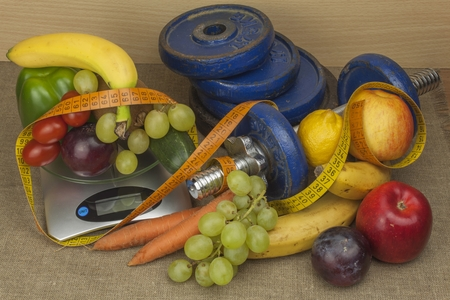 healthy sport: Chrome dumbbells Surrounded with healthy fruits and vegetables on a table. Concept of healthy eating and weight loss. Diet for athletes.