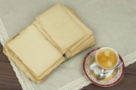 old paper background: Porcelain cup of coffee and old books. Relax over coffee. Reading old books.