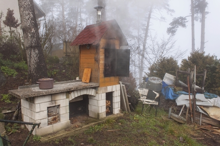 domestic production: Homemade smokehouse in the morning mist. Domestic production of sausages. Smokehouse at the house in the woods. Traditional food