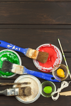 businness: Brushes and paint on a wooden table. Painter tools. Workshop painter. Needs painting. Sales painting needs. Clutter on the workbench. Sales of color. Advertising on painting.