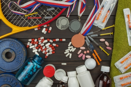 testosterone: Deception in sports. Doping for athletes. Scammers in the sport. Abuse of anabolic steroids for sports. Anabolic steroids spilled on a wooden table. Fraud in sports.